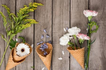Photo for Top view of beautiful flowers in waffle cones and petals on wooden background - Royalty Free Image