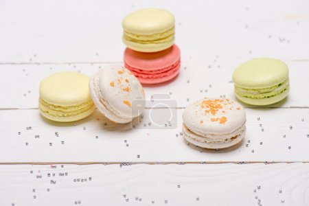 Photo for Group of beautiful colorful macarons on white wooden table. Sweets background - Royalty Free Image