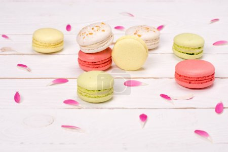 Photo for Still life of fresh macarons on the table with pink petals. sweets background concept - Royalty Free Image
