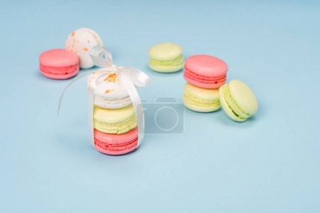 Photo for Colorful macarons tying with white ribbon for gift on blue surface. Still life of fresh macarons concept. - Royalty Free Image