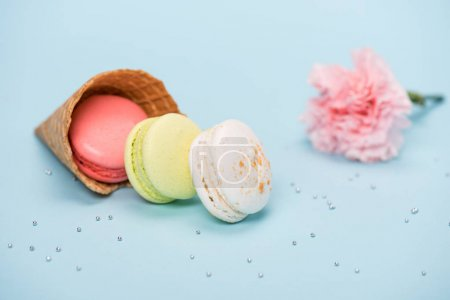 Photo for Group of handmade macarons in waffle cone and pink flower on blue surface. macarons background concept - Royalty Free Image