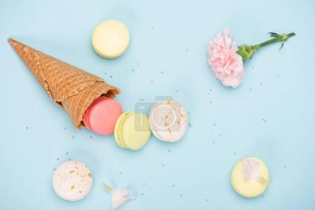 Photo for Top view of sweet macarons in waffle cone with pink Carnation. Colorful sweets background - Royalty Free Image