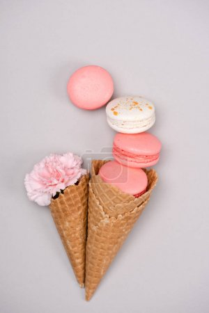Group of pink macarons with waffle cones