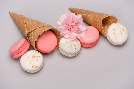 Pink and white macarons in waffle cones
