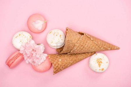 Photo for Top view of fresh macarons with waffle cones and Carnation flower on pink background. Sweets background concept - Royalty Free Image