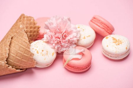Photo for Closeup of macarons group with waffle cones and Carnation flower on pink surface. Macarons background concept - Royalty Free Image