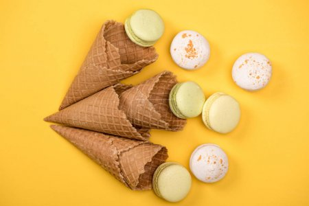 Yellow and white macarons in waffle cones