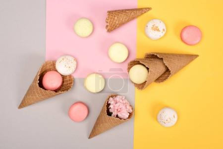 Photo for Top view of fresh homemade macarons, waffle cones and Carnation flower on colorful surface. Sweet macarons pattern concept - Royalty Free Image