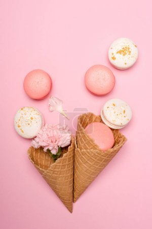 Photo for Top view of tasty macarons, waffle cones and Carnation flower on pink surface. Sweets background concept - Royalty Free Image