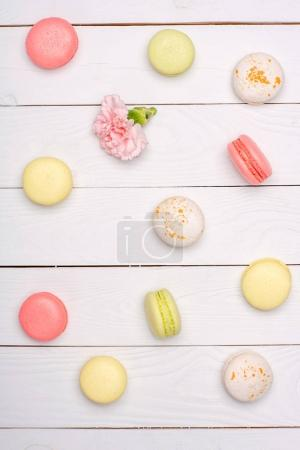Photo for Variety of fresh macaroons in waffle cones on wooden surface. Colorful macarons pattern concept - Royalty Free Image