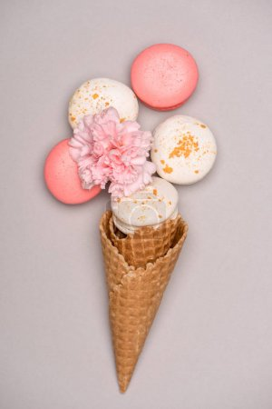 Photo for Top view of macarons in waffle cone and Carnation flower on grey. Sweets background concept - Royalty Free Image