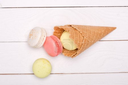 Photo for Colorful homemade macarons in waffle cones on wooden surface. sweets background - Royalty Free Image