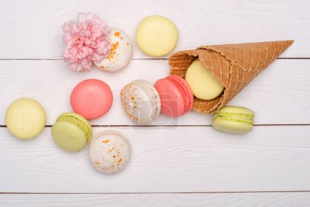 Photo for Stack of sweet macaroons and waffle cones styling with flower on wooden surface. sweets background - Royalty Free Image