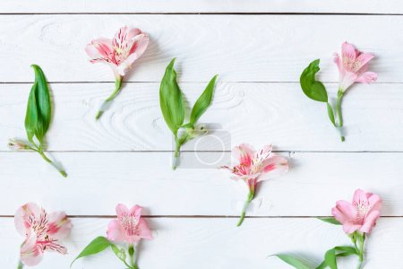 Photo for Top view of beautiful pink orchids with green leaves on wooden table - Royalty Free Image