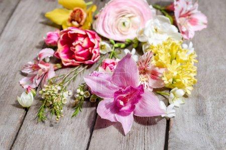 Photo pour Vue rapprochée de belles fleurs en fleurs sur une table en bois - image libre de droit