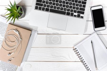 Photo for Top view of laptop, smartphone with blank screen and office supplies at workplace - Royalty Free Image