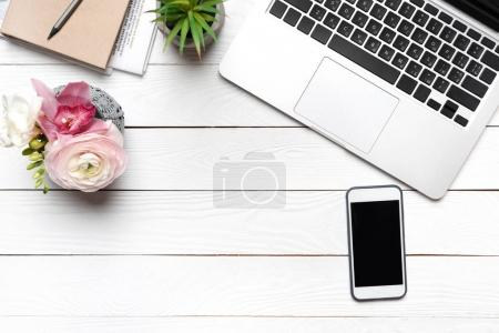 Photo for Top view of laptop, smartphone and beautiful flowers in vase on wooden table - Royalty Free Image