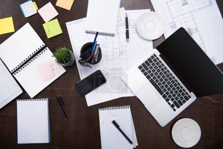 Foto de Vista superior del ordenador portátil, smartphone, blocs de notas y oficina de suministros en mesa en el espacio de trabajo - Imagen libre de derechos