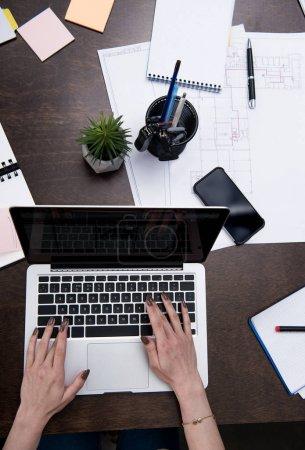 Photo pour Vue recadrée de femme d'affaires travaillant avec un ordinateur portable sur une table en bois à l'espace de travail - image libre de droit