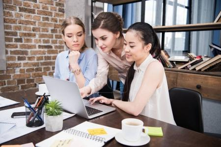 Photo for Happy multicultural businesswomen working with laptop together at workplace in modern office - Royalty Free Image