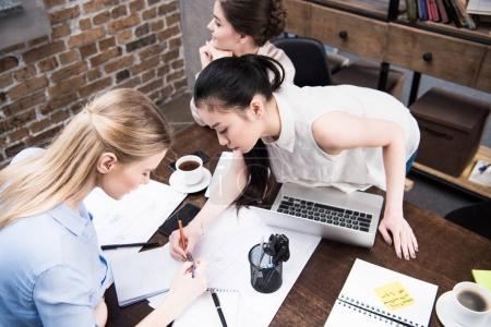Foto de Mujeres empresarias multiculturales discutir proyecto y escribir algo en el Bloc de notas junto al espacio de trabajo - Imagen libre de derechos