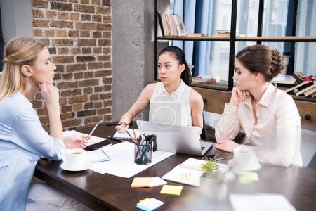 Photo pour Femmes d'affaires multiculturelles songeur discutant affaires projet sur lieu de travail avec ordinateur portable - image libre de droit