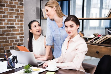 Photo for Smiling young businesswomen working with laptop and digital tablet at workplace - Royalty Free Image