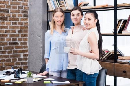 Foto de Sonriente a joven empresarias juntos de pie en el escritorio durante la pausa café - Imagen libre de derechos