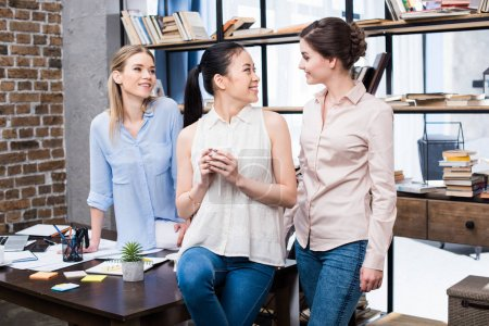Photo for Smiling young businesswomen talking at workplace while having coffee break - Royalty Free Image