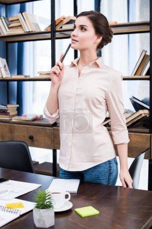 Foto de Empresaria joven pensativa con la pluma de pie en el escritorio y mirando lejos - Imagen libre de derechos