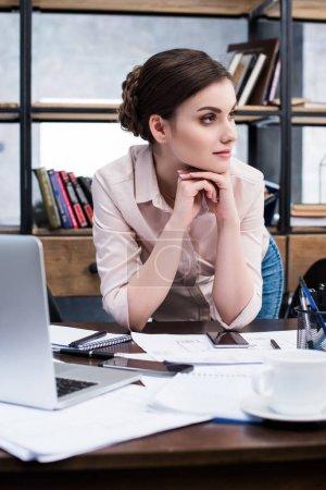 Foto de Hermosa empresaria jóvenes apoyado en la mesa con documentos y portátil mirando lejos - Imagen libre de derechos