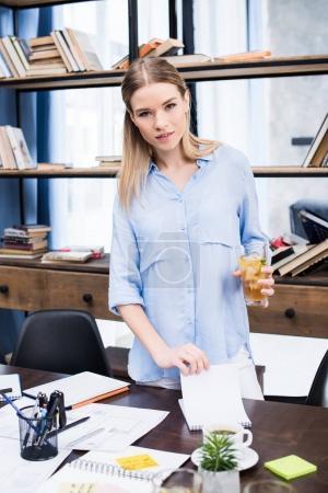 Foto de Atractivo joven empresaria sosteniendo vidrio con té helado estando en el escritorio con papeles - Imagen libre de derechos