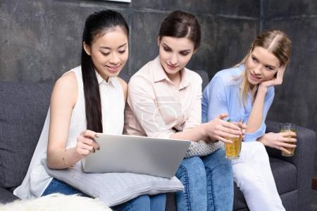 Foto de Amigos utilizando la computadora portátil mientras pasar tiempo junto con bebidas - Imagen libre de derechos