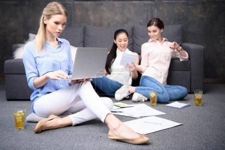 Foto de Empresaria centrada usando la laptop con sus colegas cerca de - Imagen libre de derechos