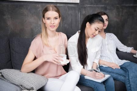 Girl writing while friends drinking coffee