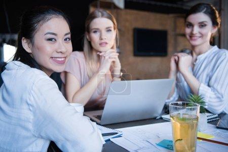 Foto de Jóvenes empresarias casuales mirando a cámara mientras trabajaba en la computadora portátil - Imagen libre de derechos