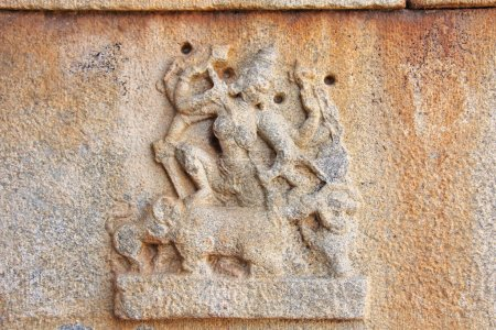 Stone bas-reliefs on the walls in Temples Hampi. Carving stone ancient background. Carved figures made of stone. Unesco World Heritage Site. Karnataka, India.