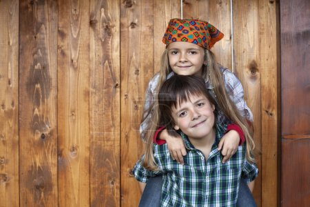 Happy kids portrait against wooden wall