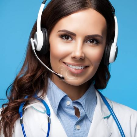happy smiling young doctor in headset, on blue