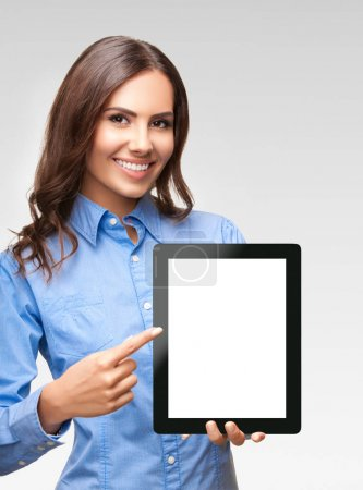 Photo for Happy smiling beautiful young businesswoman showing blank no-name tablet pc monitor, against grey background, with copyspace area - Royalty Free Image