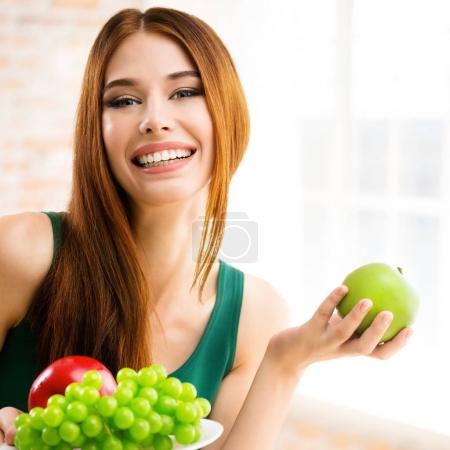 Photo for Young happy smiling woman with plate of fruits and green apple, indoors. Beauty and dieting concept. Weight lossing, by healthy eating. Square composition. - Royalty Free Image