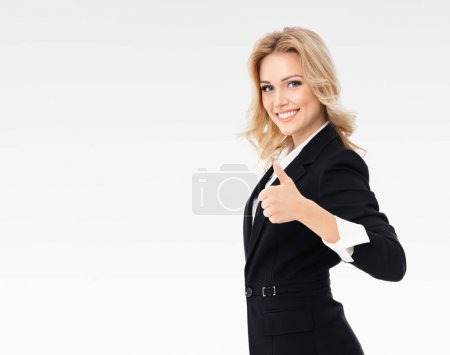Photo for Happy smiling beautiful young businesswoman showing thumbs up gesture, on grey background, with blank copyspace area for slogan or text message. Caucasian blond model in business presentation concept. - Royalty Free Image