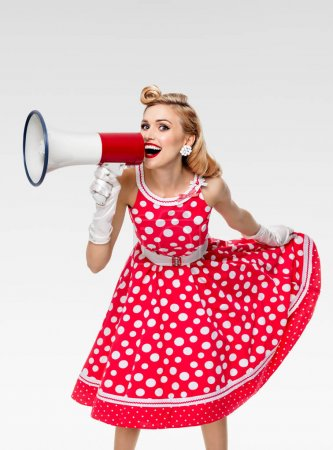 Photo for Portrait of woman holding megaphone, dressed in pin-up style red dress in polka dot and white gloves, on grey background. Caucasian blond model posing in retro fashion vintage studio shoot. - Royalty Free Image