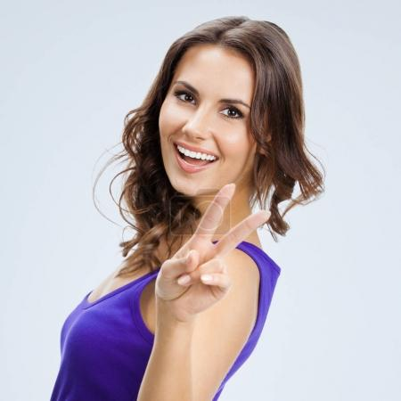 Photo for Portrait of happy smiling beautiful young woman showing two fingers or victory gesture, over grey background. Caucasian brunette model in emoshions and optimistic, positive, happy feeling concept studio shoot. Square composition. - Royalty Free Image