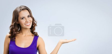 Photo for Happy smiling beautiful young woman showing copyspace or something, over grey background. Caucasian brunette model in emoshions and optimistic, positive, happy feeling concept studio shoot. - Royalty Free Image