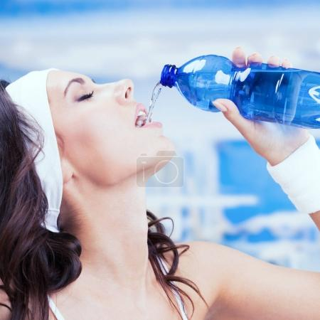 Young attractive woman drinking water, at fitness club