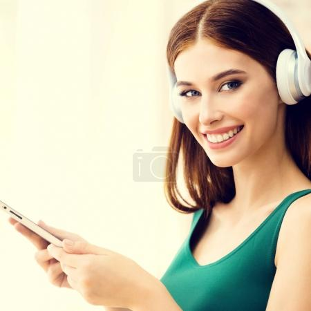 Young woman listening headphones, indoors.