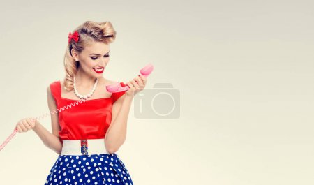 smiling woman with phone, dressed in pin-up style dress