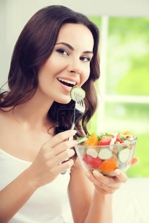 Photo for Portrait of happy smiling young brunette woman with vegetarian vegetable salad, indoors. Healthy eating, beauty and dieting concept. - Royalty Free Image