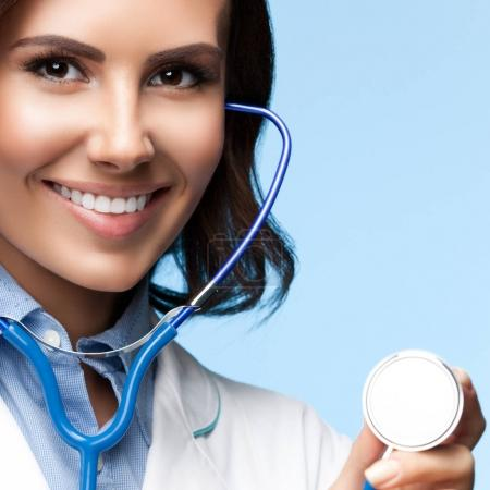 doctor with stethoscope in hand, on blue